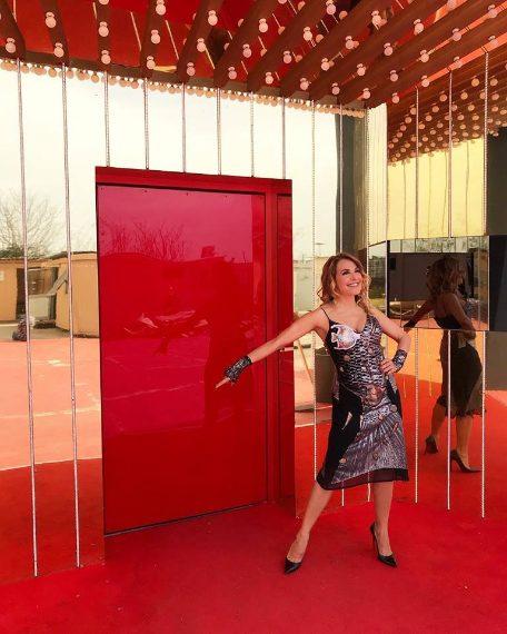 """La conduttrice pubblica una delle prime foto della sua nuova avventura al GF: """"Oggi davanti alla porta rossa della casa del Grande Fratello 15!! Con il mitico vestito pesce!!""""."""