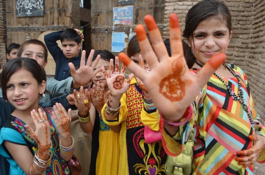 Peshawar, Pakistan. Bambine tingono le mani con l'henne per celebrare la fine del Ramadan
