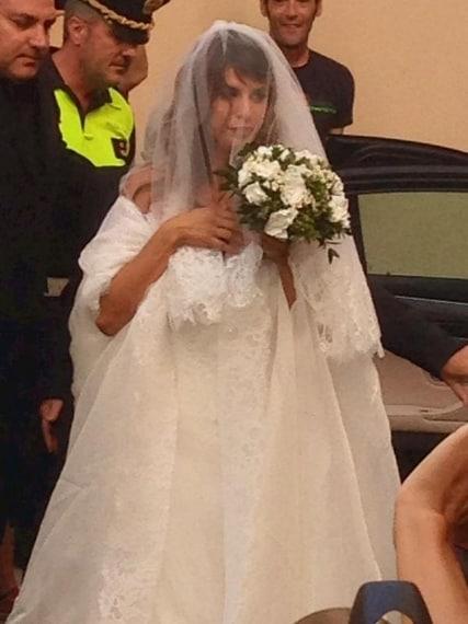 La showgirl arriva in chiesa con lungo velo profilato in pizzo e grossa stola bianca per coprire le spalle nude.