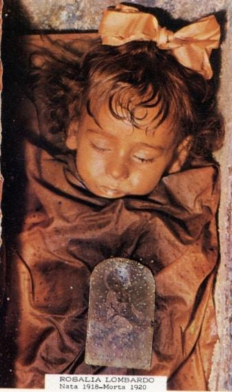 """Tra le salme delle Catacombe dei Cappuccini è particolarmente nota quella di Rosalia Lombardo. Nata a Palermo nel 1918 e ivi morta di polmonite nel 1920, la bambina è stata una delle ultime persone a essere ammesse alla sepoltura nella cripta. La bambina appare intatta tanto da destare l'impressione che stia dormendo, e da meritare il soprannome di """"Bella addormentata""""."""