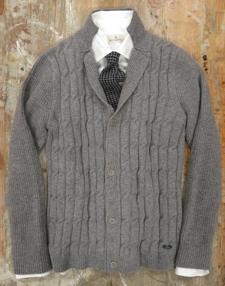 Maglia con rever a giacca in lambswool con lavorazione a treccia. Camicia sartoriale con collo a punta in cotone jacquard. Cravatta in maglia con microdisegno.