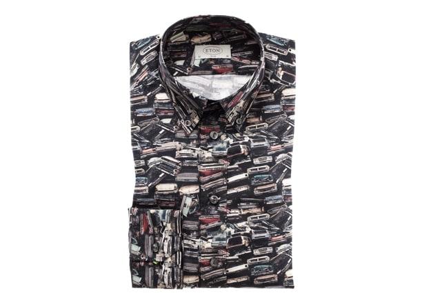 L'effetto scenografico della stampa a fantasia di macchine è proposto sulla camicia in prezioso Soho popeline: il disegno è un segno riconoscibile e geometrico che si confonde in un trompe l'oeil da artista moderno.