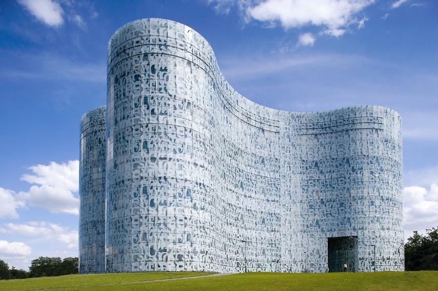 Un involucro di vetro e lettere, stampato con i caratteri di diversi alfabeti del mondo, caratterizza la biblioteca dell'Università del Brandeburgo a Cottbus, Germania, qui conosciuta come IKMZ (acronimo di Informations-, Kommunikations- und MedienZentrum).