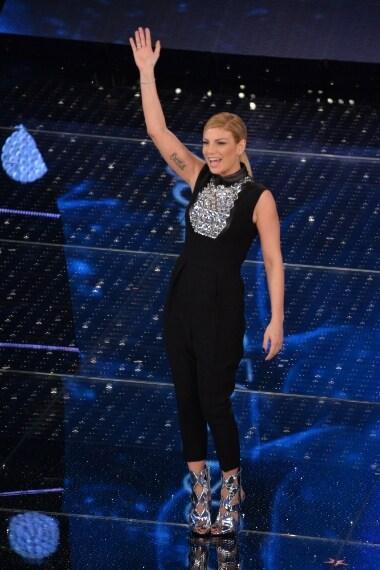 Emma indossa una jumpsuit con colletto in pelle e pantaloni crop con pinces, decorata sul décolleté da lucenti applicazioni e abbinata ad un paio di sandali traforati in silver.