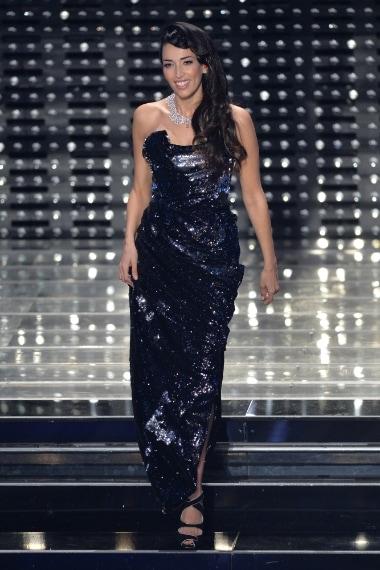Lucente e super cool, Nina Zilli sale sul palco con un abito strapless di Vivienne Westwood, con spacco laterale e drappeggi, ricoperto di paillettes dark in nero e blu.