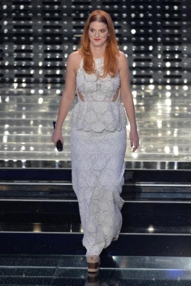 La cantante per la finale sceglie un peplum dress in pizzo bianco con baschina