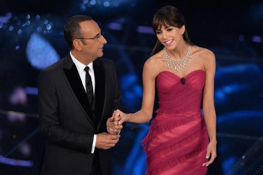 La showgirl indossa un abito strapless con coda color magenta con drappeggi di tessuto, plateau nero e collier Damiani.
