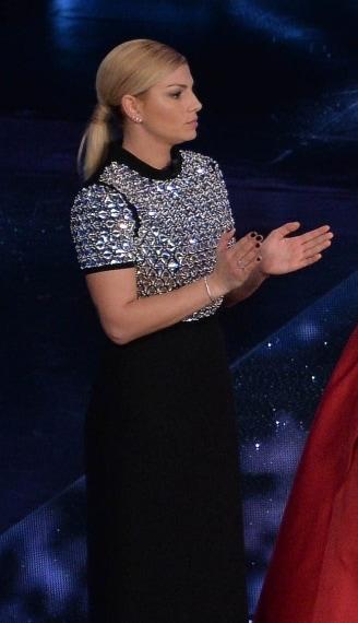 Per la seconda uscita Emma indossa un lungo abito scuro, a maniche corte e con mezzo collo, il cui corpetto è ricoperto da cristalli lucenti.