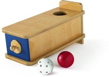 Un gioco classico del metodo Montessori, adatto anche ai bambini molto piccoli: una scatola in cui infilare una pallina nell'apposito foro per poi vederla ricomparire grazie a piccoli movimenti o a un cassetto.