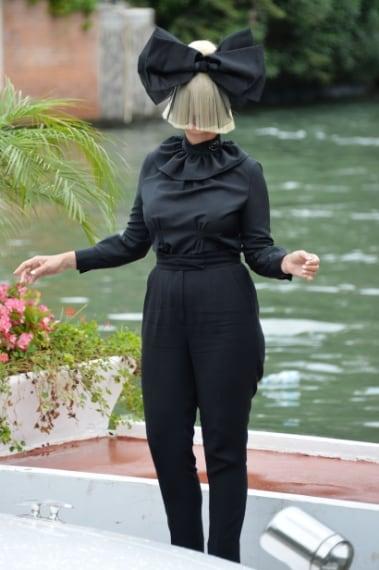 La cantante australiana Sia arriva a Venezia, coprendosi, come di consueto il viso con una parrucca bionda e un grosso fiocco nero.