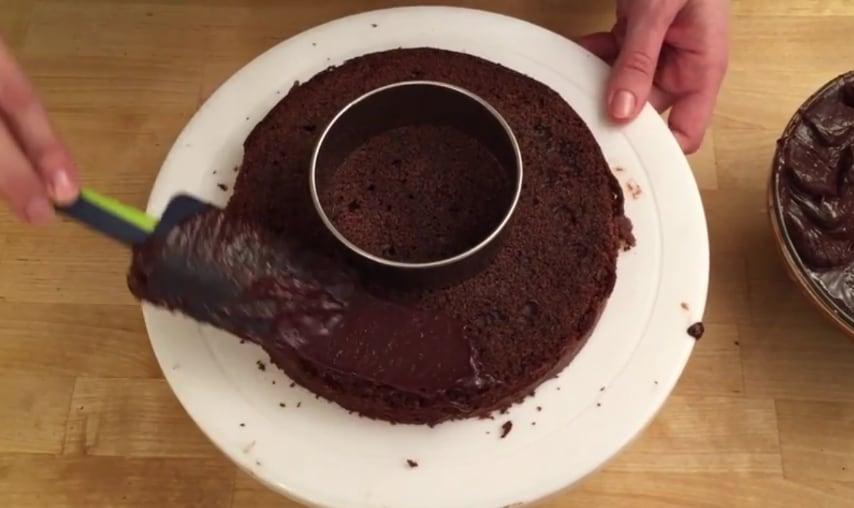 Non praticare alcun foro sulla base ma utilizzate lo strumento per il taglio circolare come limite per non spalmare la crema ganache al centro del disco di pan di spagna.