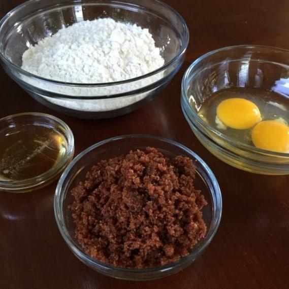 600 g di farina 2 uova 250 g di pancetta affumicata (bacon) 1 cucchiaio di grasso del bacon dopo la frittura 1-2 cucchiai d'acqua