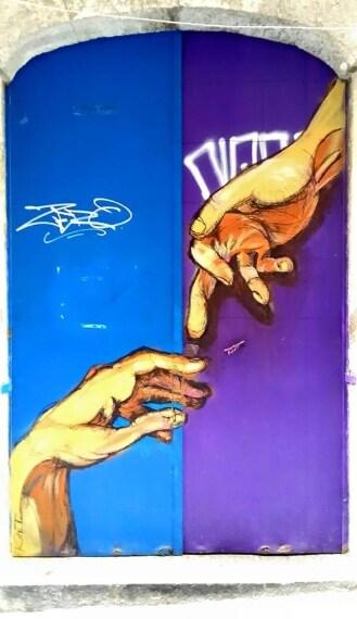 """""""Inganno della morale"""", ispirato alla """"Creazione di Adamo"""". Piccolo particolare: Dio offre il dito medio al posto dell'indice, per ricordare i diritti negati agli omosessuali in nome del moralismo. La promessa è quella di un paradiso presunto dopo la morte ma un inferno certo di diritti negati."""