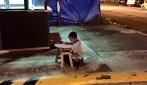 Il bambino studia alla luce del lampione: qualsiasi cosa pur di inseguire un sogno