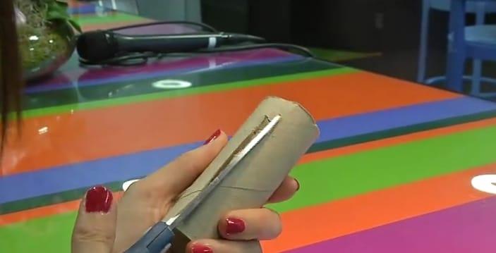Crea una fessura della dimensione del suo smartphone all'interno del rotolo di carta igienica.
