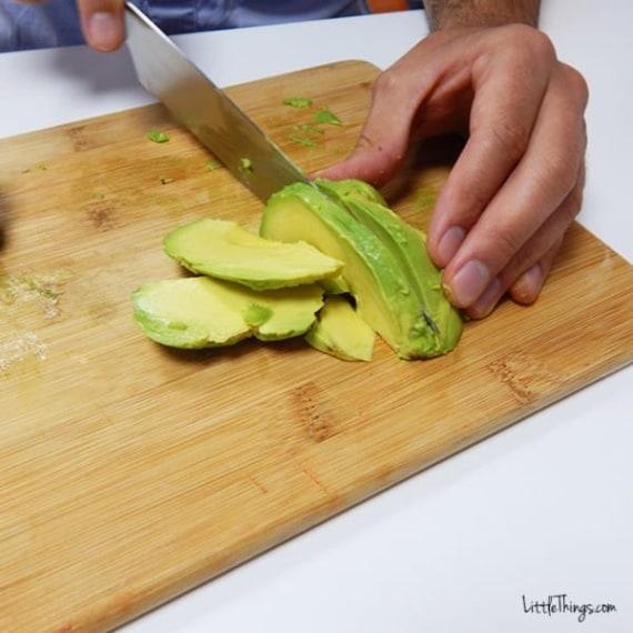 Taglia poi a fette metà avocado.