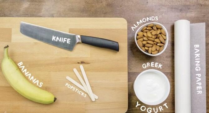 Banana, coltellaccio per sminuzzare, yogurt, mandorle, carta da forno e bastoncini.