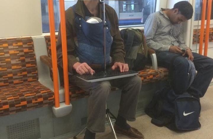 L'uomo usa un leggio per mantenere un computer portatile e una tastiera wireless.
