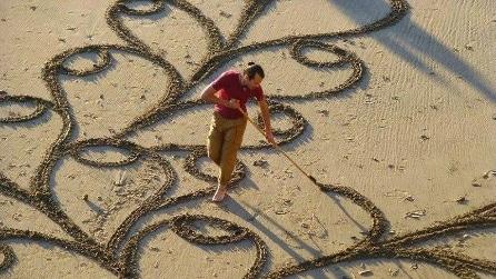 Un uomo con un rastrello sulla spiaggia: quello che realizza è strabiliante