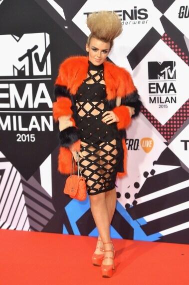 Maxi cresta, abito a rete e pelliccia arancio, la somma degli elementi è davvero too much. VOTO: 4