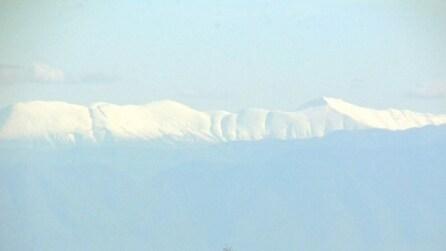 Oltre la foschia, la folgorante vista dei monti innevati dell'Albania da Capo d'Otranto