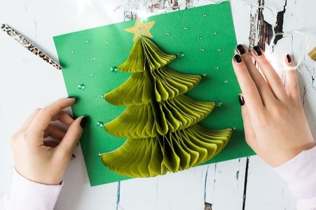 Con la carta velina sovrapposta a ventaglio si crea un fantastico albero di natale tridimensionale da inserire in un semplice cartoncino per un biglietto natalizio di sicuro effetto.