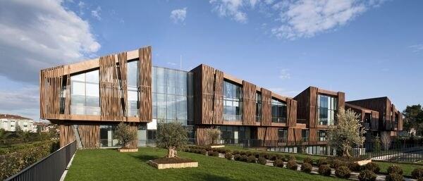 Le case si integrano tra di loro sia attraverso i giardini che le terrazze superiori o inferiori e i sentieri e gli atrii. Il colore marrone dell'esterno porta in primo piano l'effetto legno tenero e unifica la struttura.