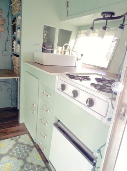 la cucina è una combinazione di stile moderno e retrò, con una stufa a propano e un mini frigorifero sotto.