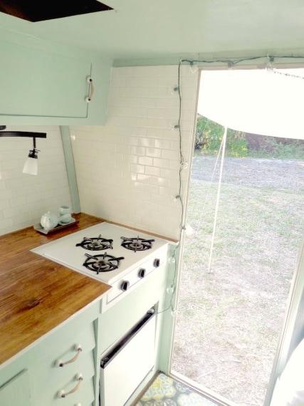 La cucina è rifinita con piastrelle bianche, fornendo un bel contrasto con pareti e armadi verde menta.