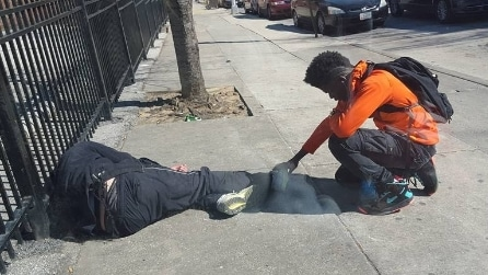 Il giovane prega per il senzatetto: la foto che ha commosso il web