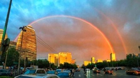Un arcobaleno sul grigio cielo di Pechino: le immagini spettacolari