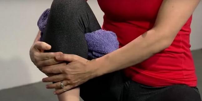Mettete l'asciugamani sotto al ginocchio e spingete il tallone su una superficie resistente