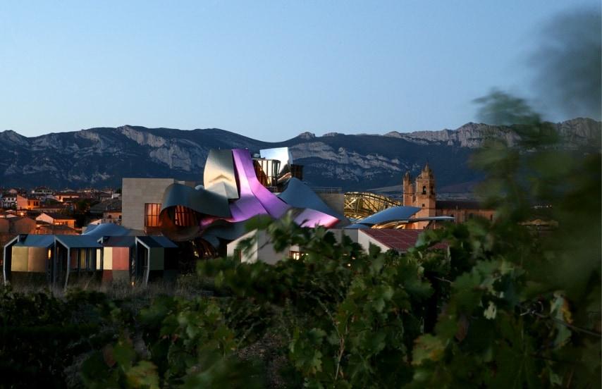 Con il profilo dei tetti in brillanti nastri di titanio rosa, oro e argento, l'hotel Marqués de Riscal, a Elciego, città del nord della Spagna, richiama il marchio di fabbrica della Gehry e associati, il celebre architetto del museo Guggenheim di Bilbao e dell'edificio Bridge of Life di Panama.