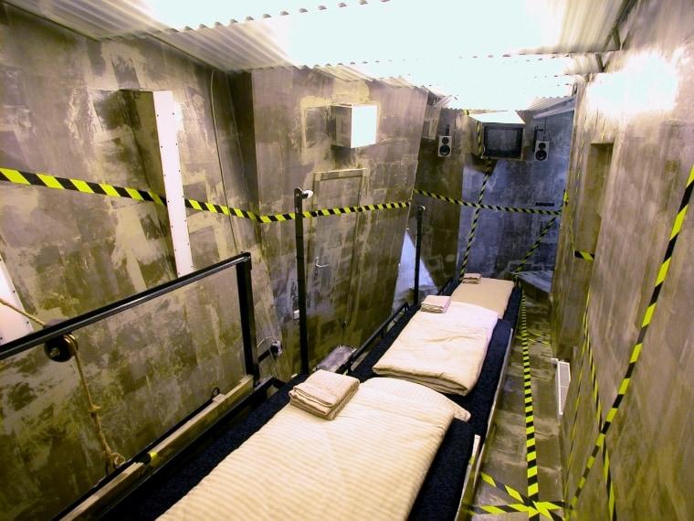 """Qui c'è una stanza capovolta con il letto sul soffitto e altre ancora in stile """"cella di prigione"""". La stanza """"Therapy"""" è completamente bianca, ma la illumina una varietà di luci colorate."""