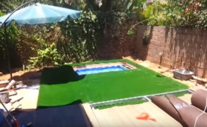 Posa dell'erba sintetica sulla copertura mobile e intorno alla piscina.
