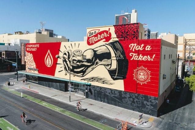 """Il leggendario artista, Shepard Fairey, ha dipinto un grande murale in uno dei più trafficati incroci di Las Vegas. Il titolo è """"Corporate Welfare?"""" ed è un invito a """"dare uno sguardo più da vicino al legame intrinseco tra le società senza volto e un governo non trasparente in una democrazia discutibile""""."""