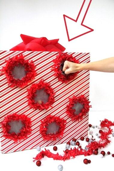 """Avete mai giocato a """"Nomi, cose e città""""? Avete presente quando bisogna scegliere la lettera e si buca un foglio con la penna? Provate a creare lo stesso sistema ma su un cartoncino; decoratelo con carta natalizie e dietro ogni buco da fare, rivestito con carta velina, inserite caramelle e dolcetti. Il calendario dell'Avvento non sarà mai stato così divertente."""