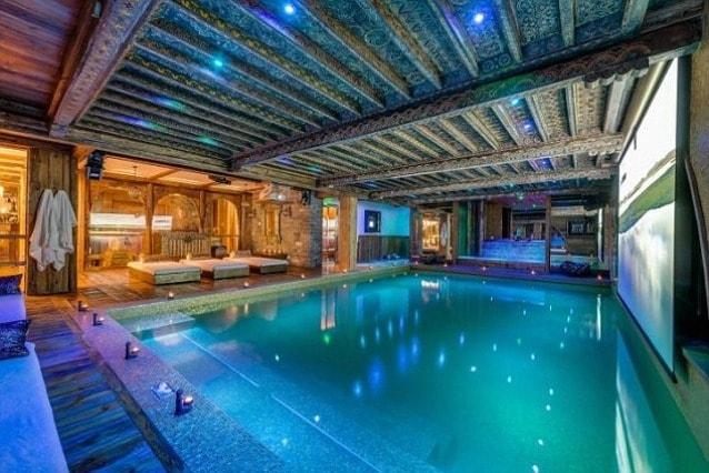 Una piscina intarsiata con riflessi oro, divani di pelle di pecora per le sei camere da letto dello Chalet Marco Polo a Val d'Isère, in Francia,