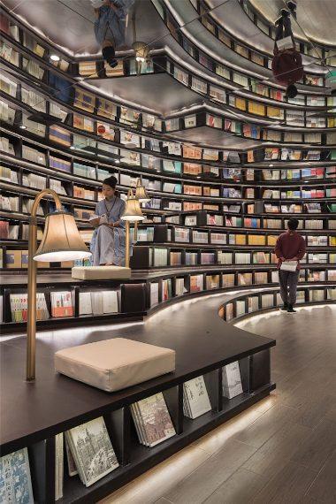 Lo spazio di questa libreria sembra ripetersi all'infinito grazie ad un gioco di specchi a agli scaffali per i libri che diventano panche, tavoli e banconi per la lettura.