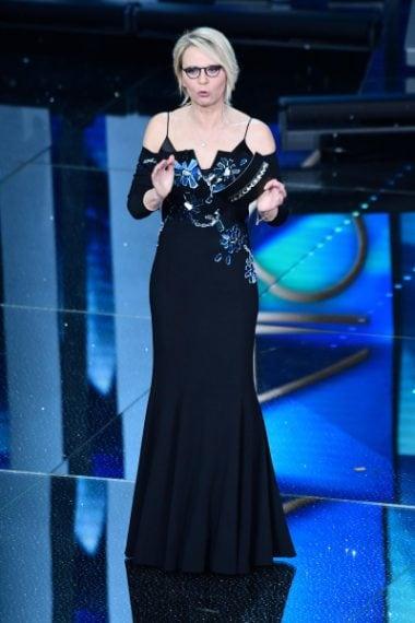 La De Filippi indossa un abito lungo nero che lascia le spalle scoperte decorato sul corpetto con specchi .