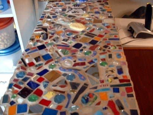 Se avete un tavolo da giardino o un vecchio tavola per la casa che non vi piace, potete fornirgli una nuova superficie d'appoggio incollando mattonelle diverse o pezzi di piastrelle insieme, a mo' di mosaico, e il tavolo vi sembrerà completamente diverso e più bello.