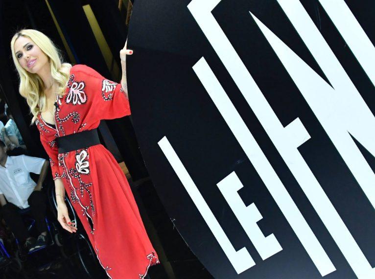La conduttrice indossa una vestaglia in seta rossa con ricamo floreale di Jucca, indossata su pantaloni neri e con cintura in vita. Completano il look décolleté Le Silla