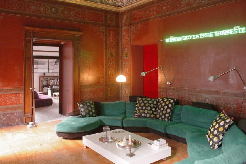 Sala rossa in stile pompeiano con soffitti affrescati e decori originari su stucco del Settecento, restaurati con cura per i disegni e i colori cangianti. In foto: sulla parete opera di Claire Fontaine