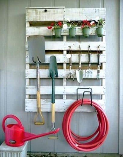Pedana in legno dipinta e usata per appendere gli attrezzi da giardino. Fonte: http://www.lushome.com/33-diyideas-reuse-recyle-wood-pallets-personalize-home-decorating/115411