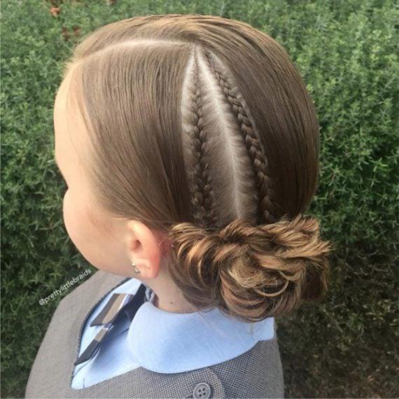 I capelli sono tirati e hanno due piccole treccine, il tutto termina in uno chignon a forma di fiore. Fonte: https://www.instagram.com/prettylittlebraids/?hl=it