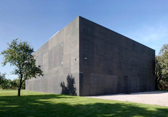 Questa casa è stata progettata da Robert Konieczny come un blocco di calcestruzzo compatto progettata con pareti scorrevoli in grado di aprirsi e chiudersi per mostrare l'abitazione interna in base alle esigenze.