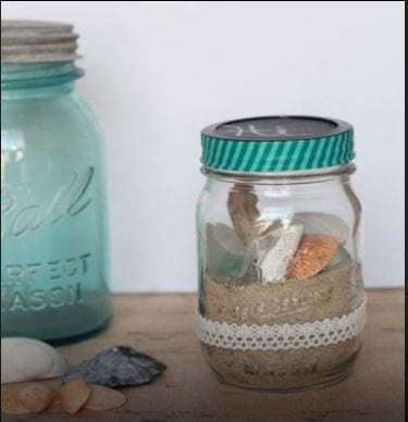 Put sand and some shells in a glass jar.