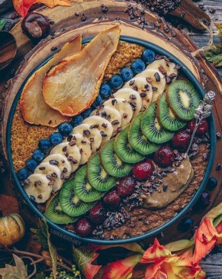 Avena calda al cioccolato con pera caramellata e budino di chia e curcuma da arricchire con banane, kiwi, more e prugne