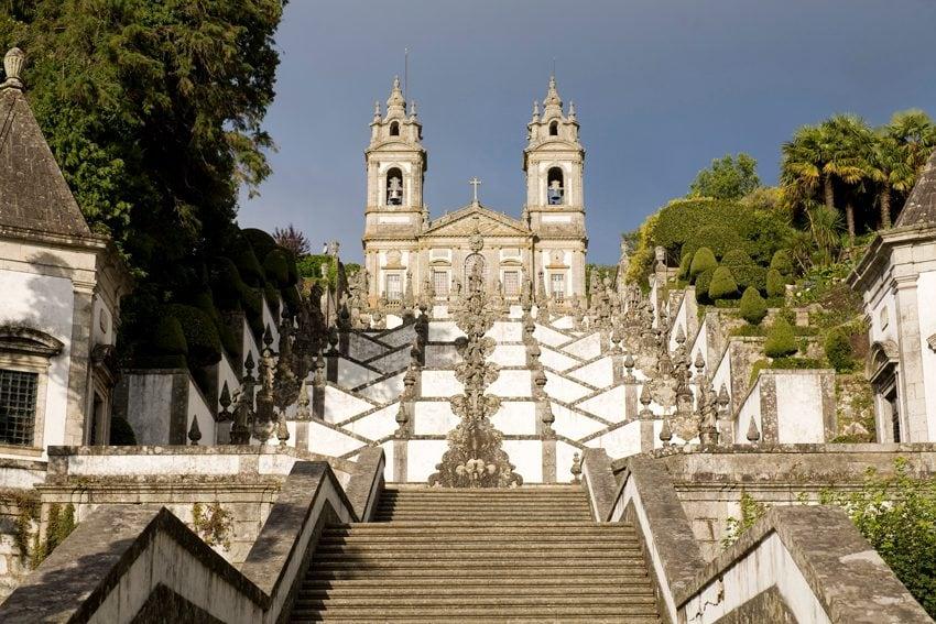 """Il santuario di Bom Jesus do Monte in Portogallo è un luogo di pellegrinaggio al di fuori della città di Braga collocato alla sommità di una stupefacente scalinata barocca all'aperto che sale per circa 120 metri di altezza. La celebre """"Escalinada"""" fa parte della Via Sacra che il pellegrino deve percorrere, possibilmente in ginocchio, per arrivare al santuario. La spettacolare scala è composta in realtà da tre differenti tratti, tutti magnifici in granito scuro e muretti in calce bianca."""