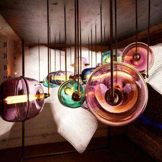 """Ini Archibong ha disegnato il lampadario Moirai multicolor fatto da tradizionali vasi in vetro soffiato a mano che possono creare combinazioni differenti per realizzare ciò che il designer chiama una """"costellazione di nuvole""""."""